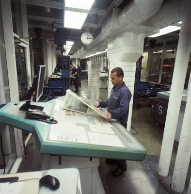 Examining a newly printed copy of 'Folha'