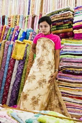Vendor modelling fabric for wedding dress in stall at Scott Market