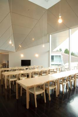 Top-floor restaurant with naked light bulbs and an angular ceiling