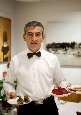 A waiter brings some mezze dishes