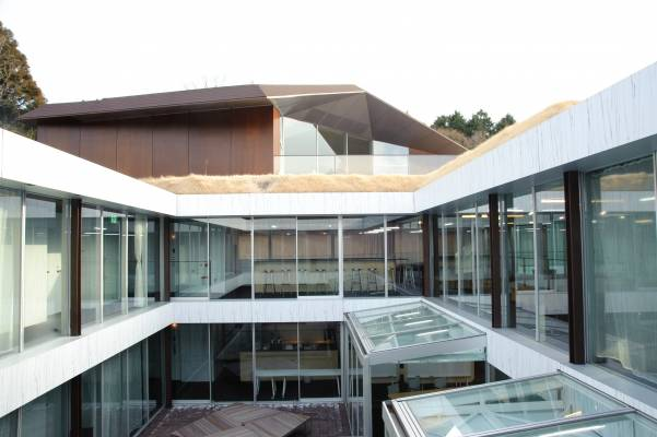 An angular roof caps the L-shaped building with two interior courtyards