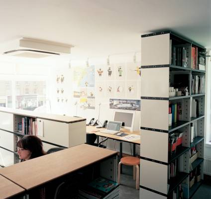 Novex shelving is used to divide the office space, Artek stools are on hand for desk guests