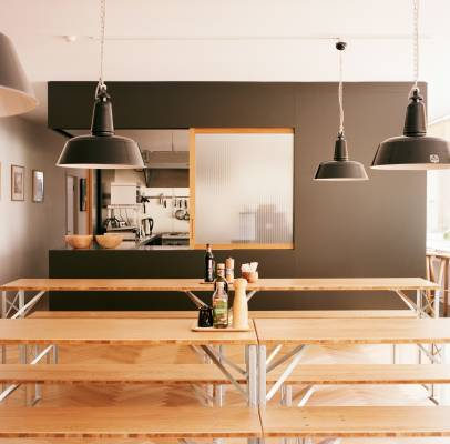 The ground floor kitchen, dining and event space has an oak parquet floor by Bauwerk, an industrial kitchen designed by Andreas Martin-Löf and built by Blumer Schreinerei. Tables and benches were custom-made by Novex and barstools are by Another Country