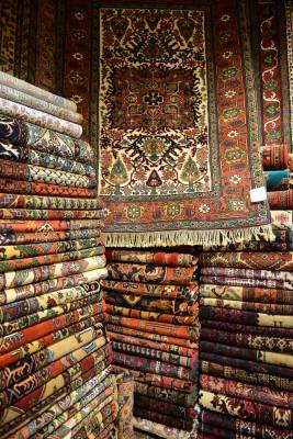 A carpet on top of stacks of fine pieces in the carpet bazaar