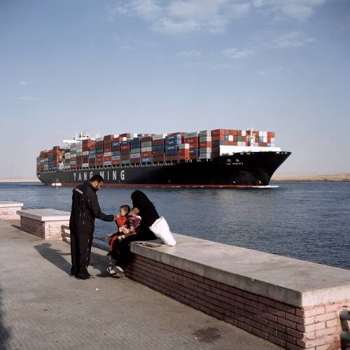 Container vessel passing through town of Suez
