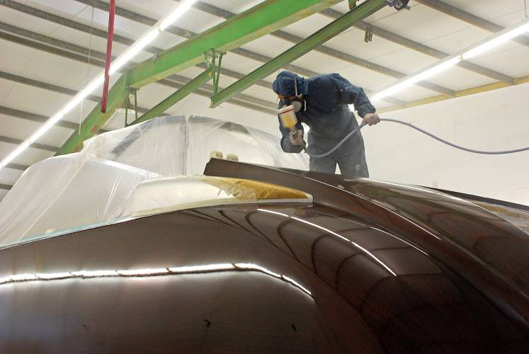 Hi-tech varnish being applied to Aguti yacht