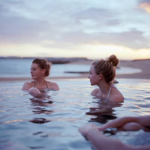 Swimmers in a geothermal pool at Ylstrondin Nautholsvik