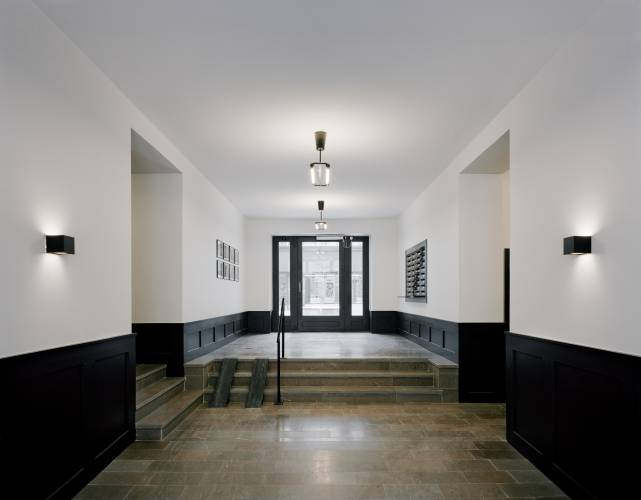 The entrance hall to Block B is a more sober affair with a polished concrete floor and a charcoal palette