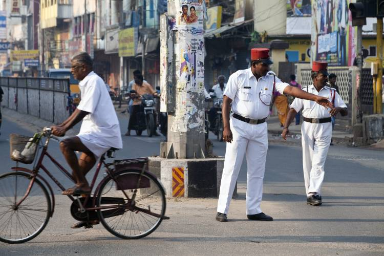 A Pondicherry policeman directs traffic wearing a French-style uniform, complete with kepi